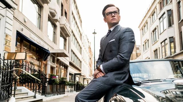 Ein junger Mann mit glatt gekämmten Haaren, Anzug und Brille sitzt auf einem Auto und blickt in die Ferne.