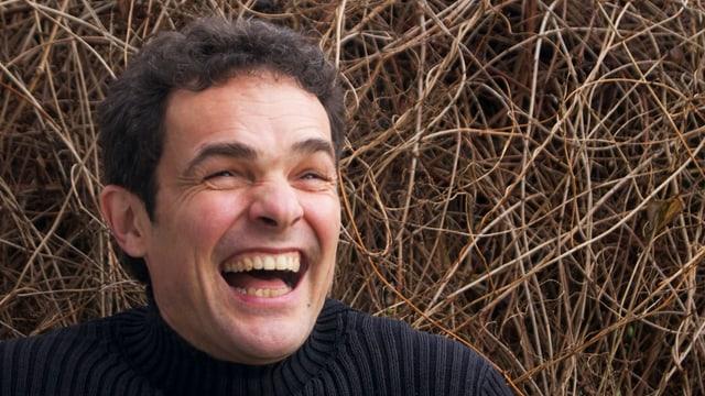 Bänz Oester lacht vor einem Busch.