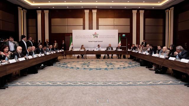 Menschen hufeisenförmig in einem Konferenzsaal postiert.