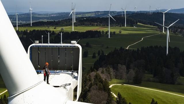Ein Mann steht auf einer Windturbine, im HIntergrund weitere Turbinen.