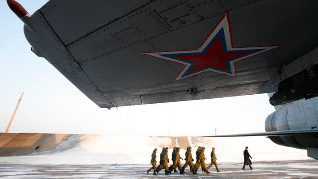 Soldaten marschieren unter einem Flugzeugflügel durch zu einer Transportmaschine