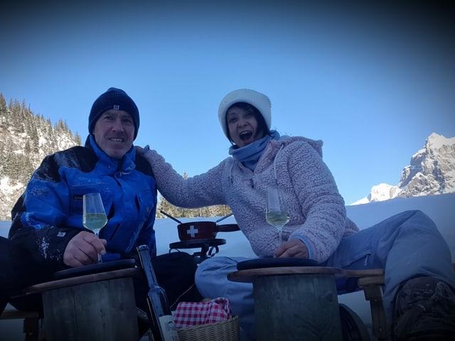 Zwei Personen verspeisen ein Fondue und trinken Prosecco.