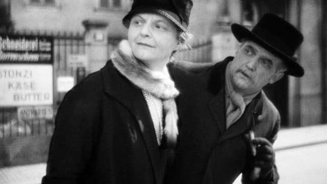 ein schwarz-weiss Bild einer Frau und eines Mannes in der Stadt