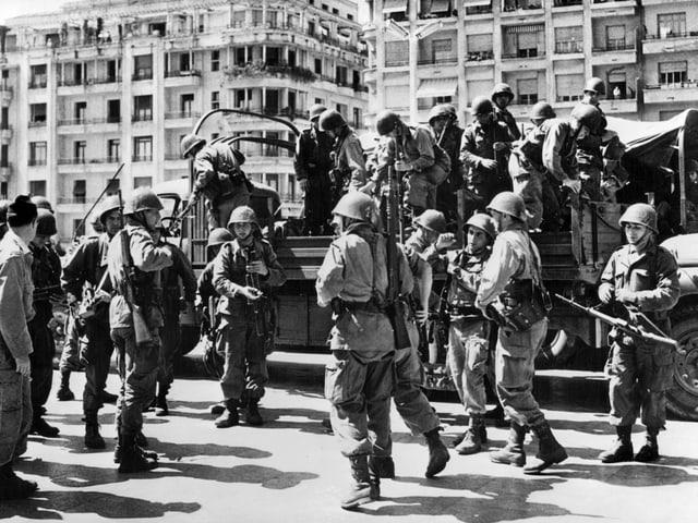 Schwarzweiss-Aufnahme, Soldaten stehen auf und um einen Lastwagen.