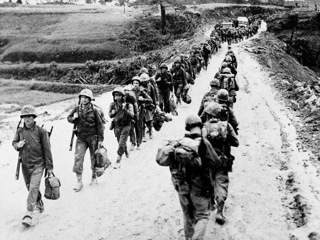 Zwei Reihen Soldaten laufen hintereinander der Kriegsfront entgegen.