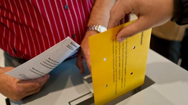 Hand wirft Wahlcouvert ein.