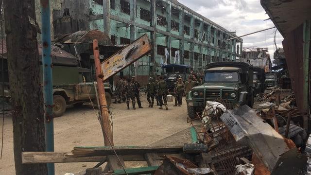 Soldaten und Armeefahrzeuge auf einer Strasse zwischen zerschossenen Häusern.