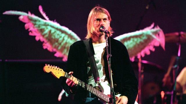 Kurt Cobain auf der Bühne. Hinter ihm sind Flügel, die auf seinem Rücken zu sein scheinen.
