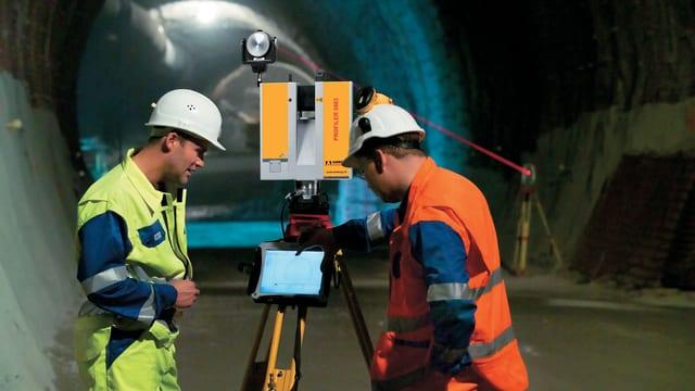 Zwei Messtechniker im Tunnel messen mit dem neuen Laser im Gotthard-Basistunnel.