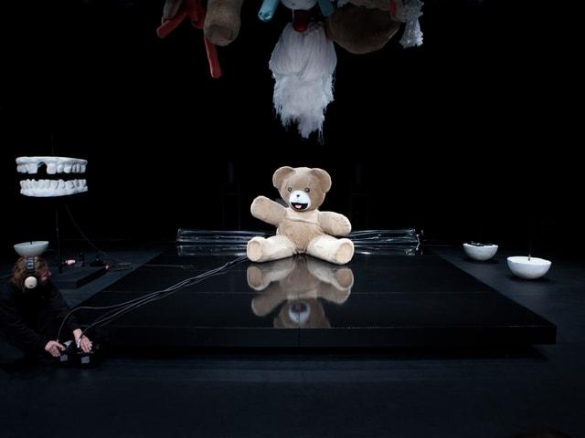 Ein überdimensionaler Teddybär sitzt auf einer Bühne.