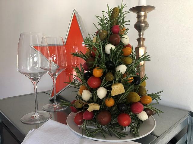 Ein Weihnachtsbaum zum Essen, die Kugeln sind aus Oliven, Cherry-Tomaten, Mozzarella-Perlen, Radieschen