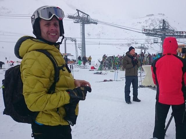 Gaudenz flury steht im Skianzug im Bereich der Bergstation auf dem Stubaiergletscher. Starker Wind wirbelt den Schnee auf.