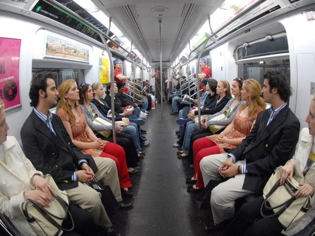 U-Bahn besetzt mit sich gegenübersitzenden eineiigen Zwillingen