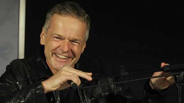 Der Autor Wolf Haas sitzt lachend vor einem Mikrofon bei einer Lesung.