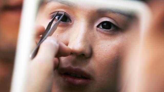 Jeman hält eine koreanischen Frau eine Pinzette an das Auge.