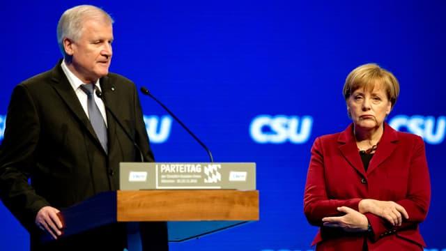 Seehofer und Merkel bei Rednerpult.