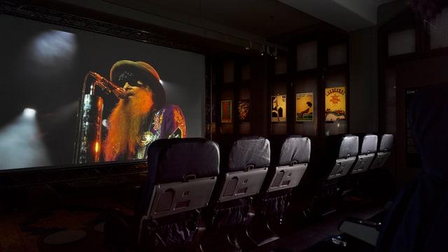 In einem kleinen Kino läuft auf einer Leinwand ein Film