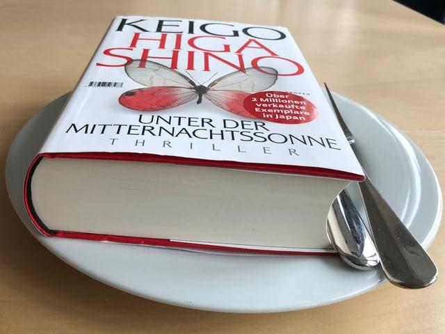 Das Buch «Unter der Mitternachtssonne» liegt auf einem weissen Teller. Messer und Gabel daneben.