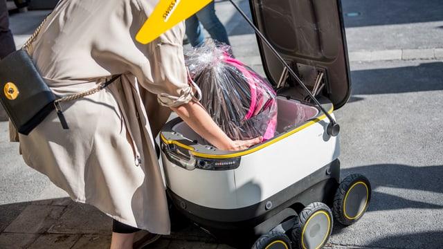 Eine Frau hebt ein Paket aus dem Innern des Roboters.