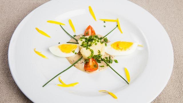 Harte Eier an Sauce mit Kartoffelstock.