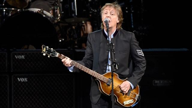 Mann mit Gitarre singt in ein Mikrofon