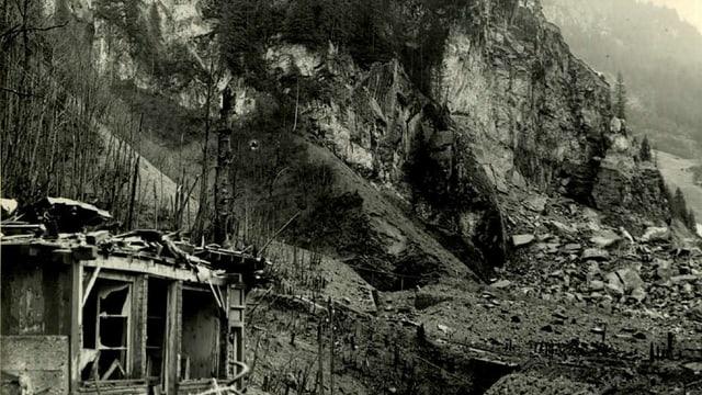 Eine Felswand mit Geröll und zerstörtem Haus.