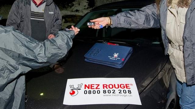 Eine Frau übergibt ihren Autoschlüssel einer Fahrerin von Nez Rouge