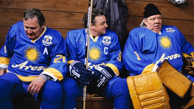 Dre alte Männer in Eishockey-Montur.