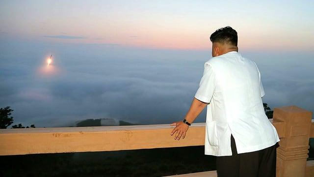 Die undatierte Aufnahme der nordkoreanischen Zentralnachrichten-Agentur zeigt den nordkoreanischen Machthaber Kim Jong Un von hinten an der Balustrade einer Terrasse stehend, während vor ihm aus dem Nebelmeer eine Rakete in den Himmel startet.