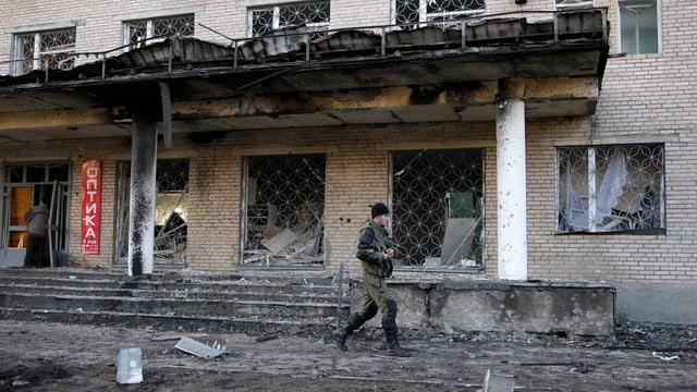 Ein pro-russischer Separatist vor einem zerstörten Gebäude