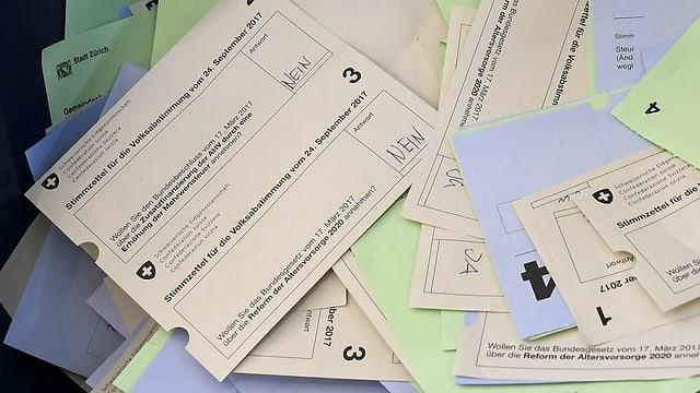 Mehrere Stimmzettel auf einem Tisch.