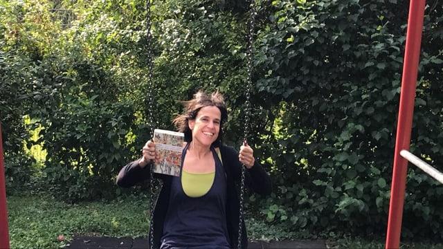 Annette König sitzt auf einer Schaukel, schwingt und hält das Buch «Liebe wird überschätzt» in der Hand
