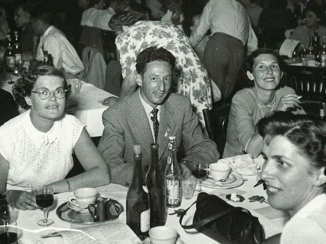 In einer Gaststätte der 1960er-Jahre sitzen mehrere Menschen mittleren Alters bei Wein und Kaffee.
