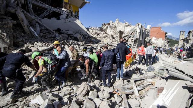 Zahlreiche retter bewegen sich vorsichtig auf den Trümmerhaufen.
