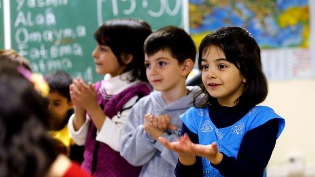 Drei Kinder stehen in einem Schulzimmer in einer Reihe, die Handflächen gegen oben gerichtet.