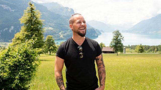 Marc Trauffer vor See- und Berglandschaft.