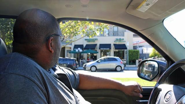 Ein Mann sitzt hinter dem Steuer eines PW und beobachtet die Gegend.