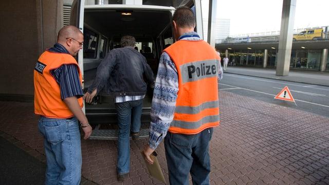 Mann steigt in Kleinbus, hinter ihm stehen Polizisten