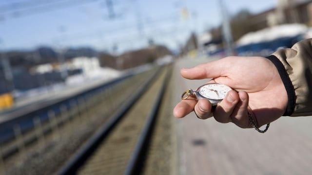 Ein Mann steht auf dem Perron und schaut auf seine Uhr