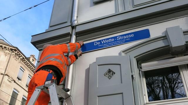 Mann montiert Schild auf Leiter