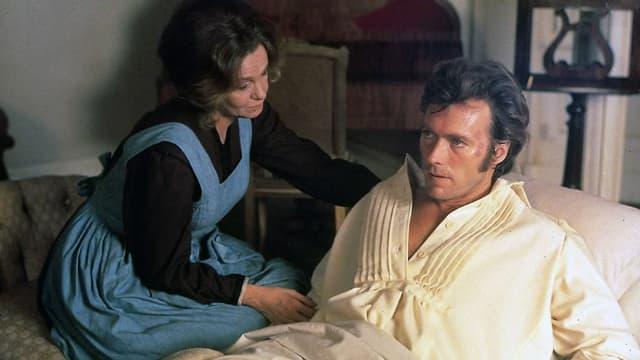 Eine Frau pflegt einen verwundeten Soldaten, der im Bett liegt.