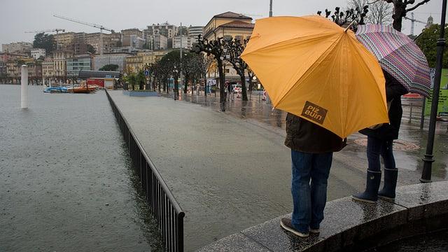 Zwei Menschen mit Regenschirmen stehen am überfluteten See in Lugano