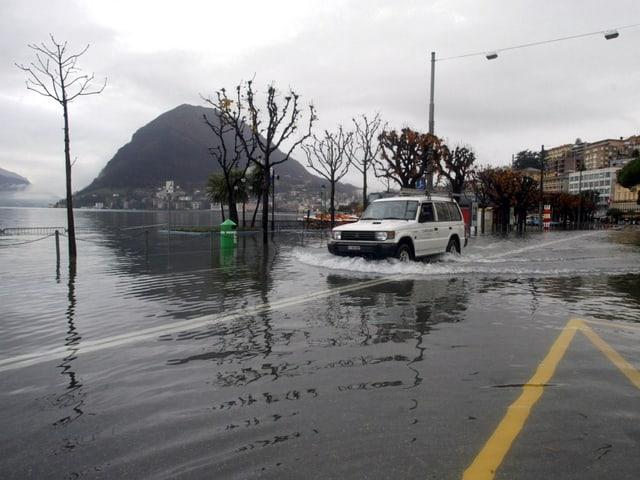 Ein Fahrzeug fährt über eine überflutete Strasse im Bereich des Luganer Sees.