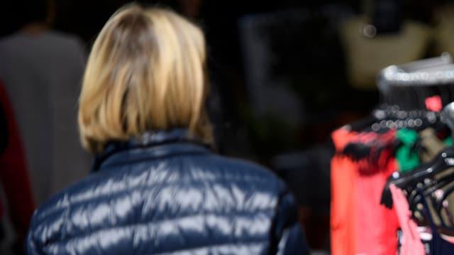 Kundin von hinten fotografiert vor einem Yendi-Geschäft mit einem Kleiderständer davor