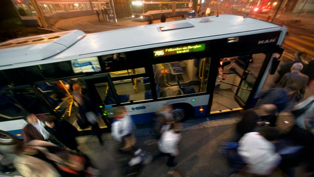 Ein Bus der VBZ, davor Pendlerinnen und Pendler.