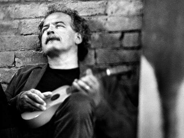 Ein Mann sitzt an einer Backsteinwand gelehnt und spielt Gitarre.