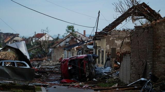 Tornado hinterlässt Trümmer von Häusern und umgekippte Autos.