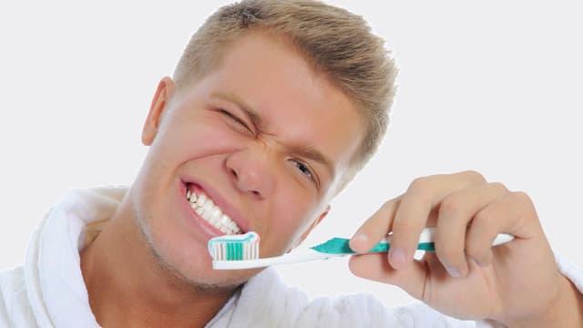Mann putzt sich die weissen Zähne.