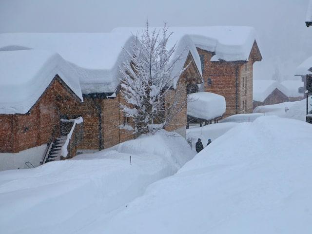 Dorf mit Holzhäusern versinkt im Schnee. Menschen laufen durch mannshohe Schneegassen.