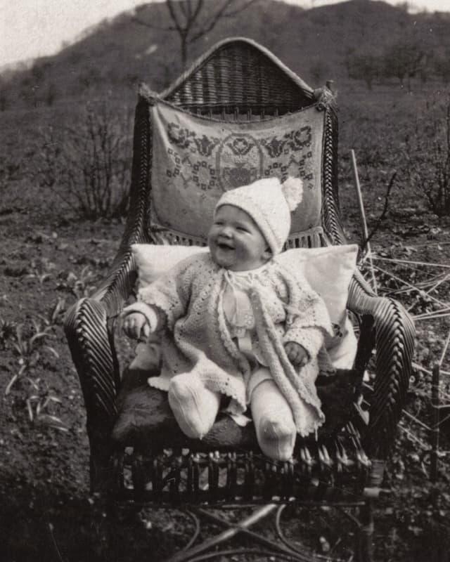 Eine Kleinkind in Strickkleidern sitzt auf einem grossen Korbstuhl.